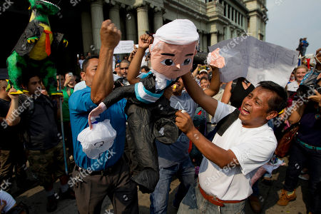 Men pound on an of effigy of Guatemalan President Otto Perez Molina during a protest sparked by a recent corruption scandal, in Guatemala City, . Juan Carlos Monzon, the private secretary of Guatemala's vice president, has been identified by the authorities as the alleged ringleader of an organization dedicated to defrauding the state through corruption and theft