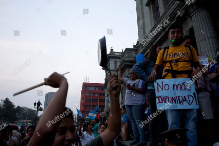 A man bangs on a pot as he joins others in a protest against Guatemalan President Otto Perez Molina, sparked by a recent corruption scandal, in Guatemala City, . Juan Carlos Monzon, the private secretary of Guatemala's vice president, has been identified by the authorities as the alleged ringleader of an organization dedicated to defrauding the state through corruption and theft