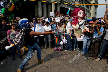 A man wearing a Lucha Libre wrestling mask swings at an effigy of Guatemalan Vice President Roxana Baldetti during a protest sparked by a recent corruption scandal, in Guatemala City, . Juan Carlos Monzon, the private secretary of Guatemala's vice president, has been identified by the authorities as the alleged ringleader of an organization dedicated to defrauding the state through corruption and theft