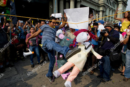 A man kicks an effigy of Guatemalan Vice President Roxana Baldetti during a protest sparked by a recent corruption scandal, in Guatemala City, . Juan Carlos Monzon, the private secretary of Guatemala's vice president, has been identified by the authorities as the alleged ringleader of an organization dedicated to defrauding the state through corruption and theft