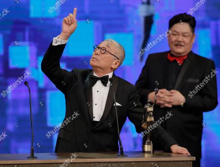Stock Photo of Kenneth Tsang Hong Kong actor Kenneth Tsang, left, reacts after winning the Best Supporting Actor Award for his role in the movie 'Overheard 3' at the 34rd Hong Kong Film Awards in Hong Kong