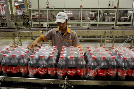 Indonesian workers inspects newly packed Coca-Cola bottles on a new production line at a bottling plant after an inauguration ceremony of two new lines attended by Coca-Cola CEO Muhtar Kent in Cibitung, West Java, Indonesia Tuesday, March, 31, 2015. The world's biggest beverage company says in its press release the inauguratio represents several major investments being made in Indonesia as part of the Coca-Cola system's plan to invest US $500 million to accelerate growth in the Indonesian market