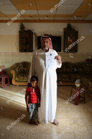 """Stock Photo of Sheikh Abdullah Ibrahim Sheikh Abdullah Ibrahim poses with his son while holding an Islamic State group-issued death certificate - all that he has left of his wife, Buthaina Ibrahim, an outspoken human rights activist and official, in the village of Eski Mosul, northern Iraq. There is no grave, no idea what was done with her body after the extremists took her from their home one night and killed her in a purge after overrunning the village north of Mosul, Iraq in June 2014. Given her government ties, IS fighters quickly demanded she apply for a repentance card. """"She said she'd never stoop so low,"""" her husband said"""