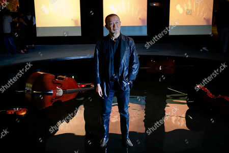 Tan Dun Chinese composer Tan Dun poses in a pool with chord instruments used for a performance as part of the Chinese pavilion 'Other Future' during the 56th Biennale of Arts in Venice