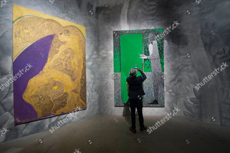 A visitor snaps pictures of the painting 'The Green Mirror' by British artist Chris Ofili on display with 'Bending Over Backwards for Justice and Peace', left, by the same author, at the 56th Biennale of Arts in Venice, Italy