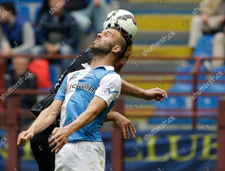 Chievo Verona's Riccardo Meggiorini, foreground, jumps for the ball with Inter Milan's Nemanja Vidic during the Serie A soccer match between Inter Milan and Chievo at the San Siro stadium in Milan, Italy