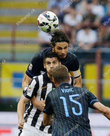 Juventus' Alvaro Morata, center, challenges for the ball with Inter Milan's Andrea Ranocchia, top, and Inter Milan's Nemanja Vidic during a Serie A soccer match between Inter Milan and Juventus, at the San Siro stadium in Milan, Italy