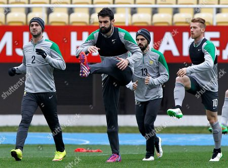 Ivan Franjic, Mile Jedinak, Aziz Behich, Oliver Bozanic Australia's national soccer team players from left, Ivan Franjic, captain Mile Jedinak, Aziz Behich and Oliver Bozanic, warm up during a training session at the Philip II Arena in Skopje, Macedonia, . Australia is preparing for the international friendly soccer match against Macedonia on Monday