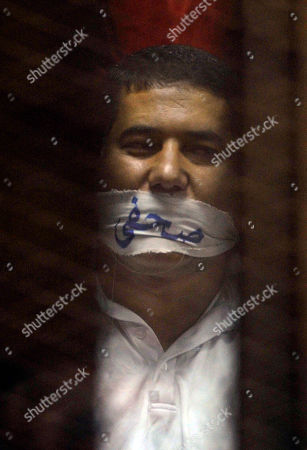 """Egyptian journalist Ibrahim el Darawy wears a cloth over his mouth with Arabic that reads, """"journalists"""" in the defendants cage of a makeshift courtroom at the national police academy, in eastern Cairo, Egypt, . An Egyptian court on Saturday sentenced ousted President Mohammed Morsi and over 100 others to death including the Brotherhood's spiritual leader, Mohammed Badie, as well as one of the Arab world's best known Islamic scholars, the Qatar-based Youssef al-Qaradawi"""