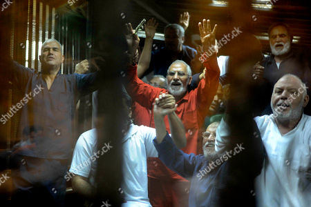Egyptian defendants including the spiritual leader of the Muslim Brotherhood, Mohammed Badie, center, make a four-fingered gesture referring to the 2013 killing of Muslim Brotherhood protesters at the Rabaah Al-Adawiya mosque, in a makeshift courtroom at the national police academy, eastern Cairo, Egypt, . An Egyptian court on Saturday sentenced ousted President Mohammed Morsi and over 100 others to death including Badie, Mohammed Beltagi, as well as one of the Arab world's best known Islamic scholars, the Qatar-based Youssef al-Qaradawi