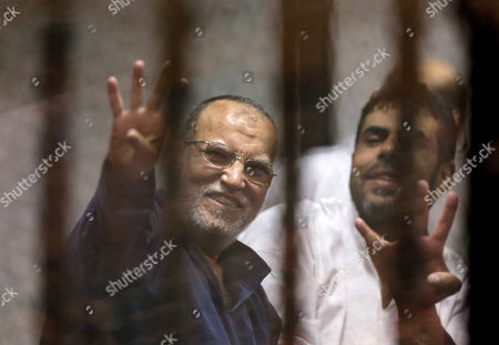 Stock Image of Essam el-Erian Senior Muslim brotherhood leader Essam el-Erian, left, flashes the four-fingered symbol of Rabaah that refers to the deadly dispersal of supporters of former Egyptian President Mohammed Morsi in August 2013, after he was sentenced to 20 years by a Cairo court, in a soundproof glass cage inside a makeshift courtroom at Egypt's national police academy, in Cairo, Egypt, . The court also sentenced Morsi to 20 years in prison over the killing of protesters in 2012, the first verdict to be issued against the country's first freely elected leader