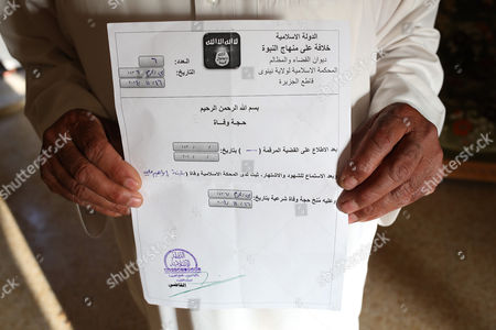 Sheikh Mohammed Abdullah Ibrahim Aatiyah holds the death certificate of his wife Buthaina. His wife was assassinated by the Islamic State group who then handed out the death certificate to Aatiyah in Mosul, Iraq