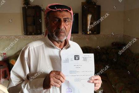 Stock Image of Sheikh Mohammed Abdullah Ibrahim Aatiyahholds the death certificate of his wife Buthaina. His wife was assassinated by the Islamic State group who then handed out the death certificate to Aatiyah in Mosul, Iraq