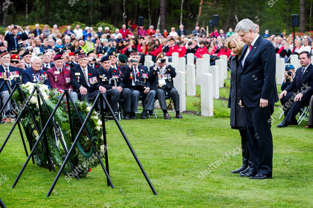 Canadian Prime Minister Stephen Harper, right, and his wife Laureen Harper observe a moment of silence after laying a wreath during memorial ceremonies in honor of Canadian soldiers who died during the liberation of the Netherlands in 1945 at the Canadian War Cemetery in Holten, east Netherlands, . Harper is in the Netherlands to mark the 70th anniversary of the Liberation of the Netherlands