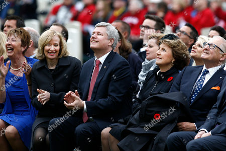 Canadian Prime Minister Stephen Harper, center, his wife Laureen Harper, second left, Netherlands' Princess Margriet, second right, and her husband Pieter van Vollenhoven, right, look up at a Spitfire flyover as they attend a memorial ceremony in honor of Canadian soldiers who died during the liberation of the Netherlands in 1945 at the Canadian War Cemetery in Holten, east Netherlands, . Harper is in the Netherlands to mark the 70th anniversary of the Liberation of the Netherlands