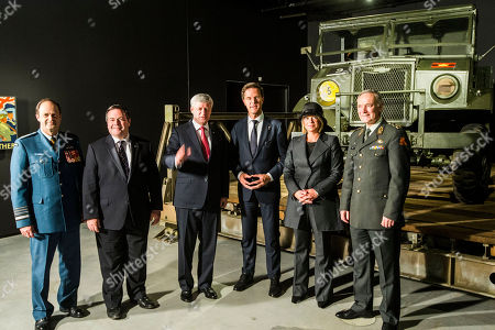 From right, Dutch commander of the armed forces Gen. Tom Middendorp, Dutch Defense Minister Jeanine Hennis-Plasschaert, Dutch Prime Minister Mark Rutte, Canadian Prime Minister Stephen Harper, Canadian Defence Minister Jason Kenney and Canadian chief of the Defense Staff Thomas Lawson pose for a photo during a meeting at the National Military Museum in Soest, central Netherlands, . Rutte and Harper are meeting to kick off a week of celebrations and remembrances to mark the 70th anniversary of the liberation of the Netherlands at the end of World War II