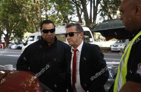 AC/DC drummer Phil Rudd, center, arrives at a court in Tauranga, New Zealand . Rudd pleaded guilty to a charge of threatening to kill a man who used to work for him. He also pleaded guilty to possessing methamphetamine and marijuana
