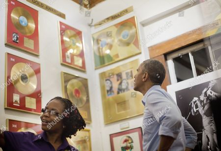 Barack Obama, Natasha Clark U.S. President Barack Obama, right, looks at selection of Bob Marley's gold records during his unannounced visits to the Bob Marley Museum led by tour guide Natasha Clark, left, in Kingston, Jamaica