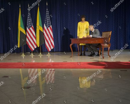 Barack Obama, Natasha Clark President Barack Obama, accompanied by Jamaican Prime Minister Portia Simpson-Miller, signs the guest book prior to their bilateral meeting at the Jamaica House, in Kingston, Jamaica