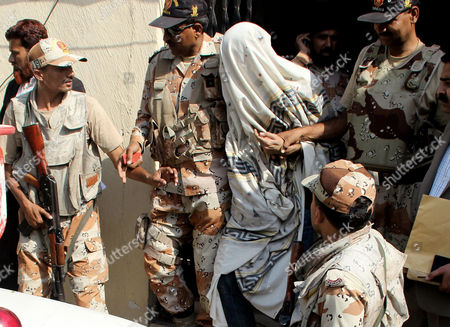 Stock Picture of Security officials escort a key suspect identified as Moazzam Ali, to a anti-terrorist court, in Karachi. Pakistan's interior minister says security forces have arrested a key suspect in the slaying of a prominent Pakistani politician Imran Farooq, who was stabbed to death in broad daylight in London in 2010