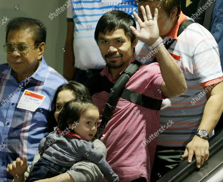 Stock Picture of Manny Pacquiao, Jinkee Pacquiao, Israel Pacquiao Filipino boxer and Congressman Manny Pacquiao waves to the crowd upon arrival with his family including his wife Jinkee and youngest son Israel (bottom left) at the Ninoy Aquino International Airport at suburban Pasay city south of Manila, Philippines. Pacquiao, who was defeated by Floyd Mayweather Jr. in their welterweight fight in Las Vegas May 2, faces lawsuits allegedly for not disclosing his shoulder injury before the fight