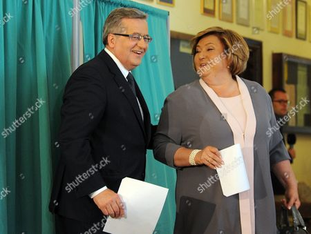 Bronislaw Komorowski, Anna Komorowska Polish President Bronislaw Komorowski and his wife Anna hold their ballots before voting in the first round of the presidential election in Warsaw, Poland, . The Poles are voting for president in nationwide balloting that is expected to see incumbent Komorowski, re-elected, but not in the first voting round