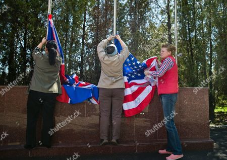 Employees raise the US and British flags while preparing for the arrival of Supreme Allied Commander Europe, General Philip Breedlove at the defense ministry headquarters in Bucharest, Romania, . Breedlove, NATO's supreme commander in Europe, said a convoy of U.S. troops crossing eastern Europe is a way of reassuring allies of the military alliance's support and of practicing little-used skills