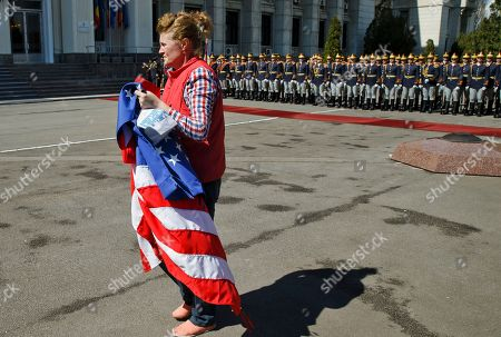 A woman carries the US flag while preparing for the arrival of Supreme Allied Commander Europe, General Philip Breedlove at the defense ministry headquarters in Bucharest, Romania, . Breedlove, NATO's supreme commander in Europe, said a convoy of U.S. troops crossing eastern Europe is a way of reassuring allies of the military alliance's support and of practicing little-used skills