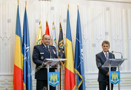 NATO's Supreme Allied Commander Europe, General Philip Breedlove, left, speaks during a joint media briefing with Romanian Defense Minister Mircea Dusa, right, in Bucharest, Romania, . Breedlove said a convoy of U.S. troops crossing eastern Europe is a way of reassuring allies of the military alliance's support and of practicing little-used skills