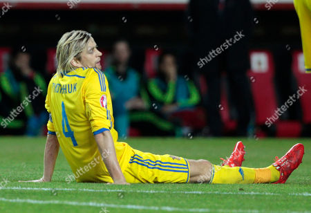 Ukraine's Anatoliy Tymoshchuk sits on the ground during the Euro 2016 qualifying soccer match between Spain and Ukraine, at the Ramon Sanchez Pizjuan stadium, in Seville, Spain, on