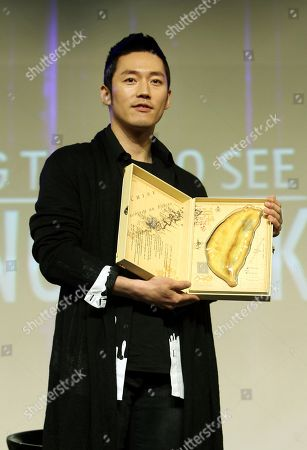 Stock Image of Jang Hyuk South Korean actor Jang Hyuk holds a Taiwanese pineapple cake and poses to the press during a media event before a meeting with his fans in Taipei, Taiwan