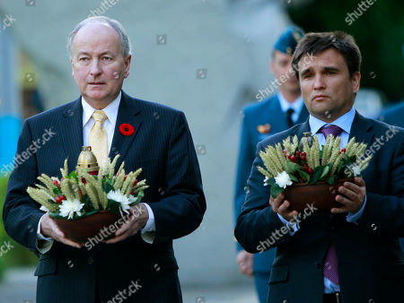 Pavlo Klimkin, Rob Nicholson Ukrainian Foreign Minister, Pavlo Klimkin, right, and Canada's Foreign Minister Rob Nicholson, left, carry bouquets to the monument to honour victims of the Great Famine, during his visit, in Kiev, Ukraine