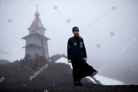 Russian Orthodox priest Sophrony Kirilov, 38, poses for a photo in front of the Holy Trinity Church, on top of a rocky hill on King George Island, Antarctica. Clad in a loose black robe and a vest dotted with patches of penguins and seals, marking his four years of service at the bottom of the world, Kirilov says there is no place he feels closer to God