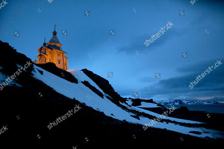 """The Holy Trinity Church located on top of a rocky hill is illuminated on King George Island, Antarctica. The clapboard church was first built in Russia, then disassembled and shipped log-by-log, """"like Lego blocks,"""" to Antarctica, said Alejo Contreras, a Chilean Antarctic explorer who witnessed the construction and consecration in 2004"""