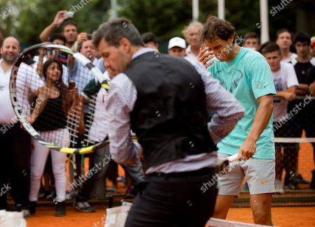 Spain's tennis player Rafael Nadal, behind right, laughs as he plays an exhibition game with Argentina's media personality Marcelo Tinelli, who holds an oversized racket, in Buenos Aires, Argentina, . Nadal is in Argentina for the Argentina Open