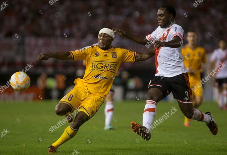 Joffre Guerron of Mexico's Tigres, left, fights for the ball with Eder Alvarez Balanta of Argentina's River Plate at a Copa Libertadores soccer match in Buenos Aires, Argentina