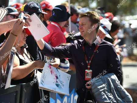 F1autoz15 Former racing driver Allan McNish of Britain signs autographs for fans ahead of the Australian Formula One Grand Prix at Albert Park in Melbourne, Australia