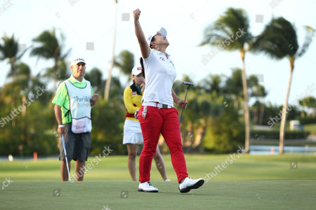 Stock Picture of Sei Young Kim Second place finisher Sun Young Yoo of South Korea, background in yellow, watches Sei Young Kim of South Korea, pump her fist in the air after winning the Pure Silk Bahamas LPGA Classic at the Ocean Club Golf Course, in Paradise Island, Bahamas