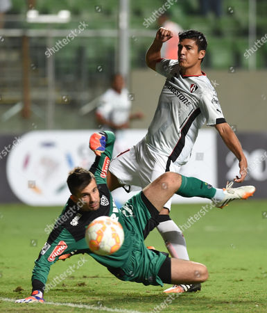 Luis Venegas, Victor Luis Venegas of Mexico's Atlas, top, fails to score as Brazil's Atletico Mineiro goalkeeper Victor watches the ball as he breaks his fall on the pitch, during a Copa Libertadores soccer game in Belo Horizonte, Brazil, . Atlas won 1-0