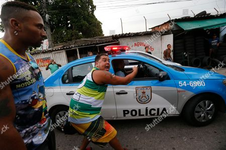 A protester points to a Pacifying Police Unit (UPP) patrol and shouts that they are just as guilty for the death of Diego da Costa, a motorcycle delivery man who was shot dead by an UPP police officer, when da Costa, unarmed, failed to stop at a check station, in Rio de Janeiro, Brazil, . About 500 motorcycle delivery men, commonly known as motoboys, protested after da Costa's burial, asking for justice and complaining of heavy-handed police tactics that have ended in the deaths of several residents