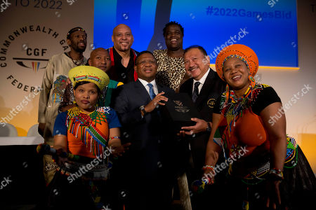 Stock Photo of South Africa's Minister of Sport and Recreation Fikile Mbalula, center left, holds candidate city Durban's 2022 Commonwealth Games bid book with President of the Commonwealth Games Federation Malaysia's Prince Imran, center right, as they pose for a group photograph with cultural performers at the end of the formal bid presentation from the South African city of Durban to host the 2022 Commonwealth Games at Mansion House in London