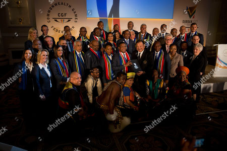 South Africa's Minister of Sport and Recreation Fikile Mbalula, center left, holds candidate city Durban's 2022 Commonwealth Games bid book with President of the Commonwealth Games Federation Malaysia's Prince Imran, center right, as they pose for a delegation photograph at the end of the the formal bid presentation from the South African city of Durban to host the 2022 Commonwealth Games at Mansion House in London