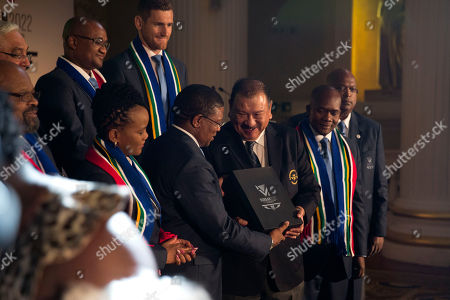 South Africa's Minister of Sport and Recreation Fikile Mbalula, center left, presents candidate city Durban's 2022 Commonwealth Games bid book to President of the Commonwealth Games Federation Malaysia's Prince Imran, center right, at the end of the the formal bid presentation from the South African city of Durban to host the 2022 Commonwealth Games at Mansion House in London