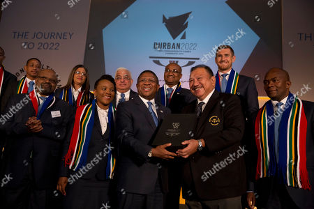 South Africa's Minister of Sport and Recreation Fikile Mbalula, center left, holds candidate city Durban's 2022 Commonwealth Games bid book with President of the Commonwealth Games Federation Malaysia's Prince Imran, center right, as they pose for a group photograph at the end of the the formal bid presentation from the South African city of Durban to host the 2022 Commonwealth Games at Mansion House in London