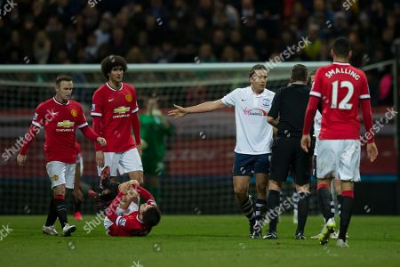 Preston's Kevin Davies, centre right, remonstrates with referee Phil Dowd before receiving a yellow card after a tackle on Manchester United's Abder Herrera, bottom left, during the English FA Cup Fifth Round soccer match between Preston and Manchester United at Deepdale Stadium in Preston, England