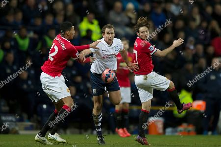 Preston's Kevin Davies, centre, fights for the ball against Manchester United's Chris Smalling, left, and Daley Blind during the English FA Cup Fifth Round soccer match between Preston and Manchester United at Deepdale Stadium in Preston, England