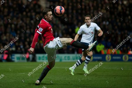 Manchester United's Wayne Rooney, left, controls a ball as Preston's Kevin Davies looks on during the English FA Cup Fifth Round soccer match between Preston and Manchester United at Deepdale Stadium in Preston, England