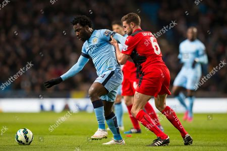 Manchester City's Wilfried Bony, left, fights for the ball against Leicester's Matthew Upson during the English Premier League soccer match between Manchester City and Leicester City at the Etihad Stadium, Manchester, England