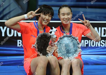 China's Bao Yixin and Tang Yuanting, left, celebrate with the trophy after beating China's Wang Xiaoli and Yu Yang 21-14, 21-14 during the Women's Doubles final, at the All England Badminton Championships in Birmingham, England