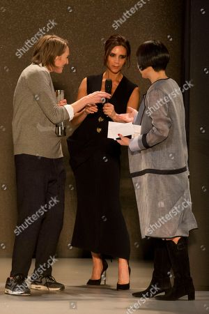 Stock Photo of Angelica Cheung, editor-in-chief for Vogue China and Victoria Beckham, centre, present the International Woolmark Prize for womenswear to winner Marcia Patmos in Beijing, China